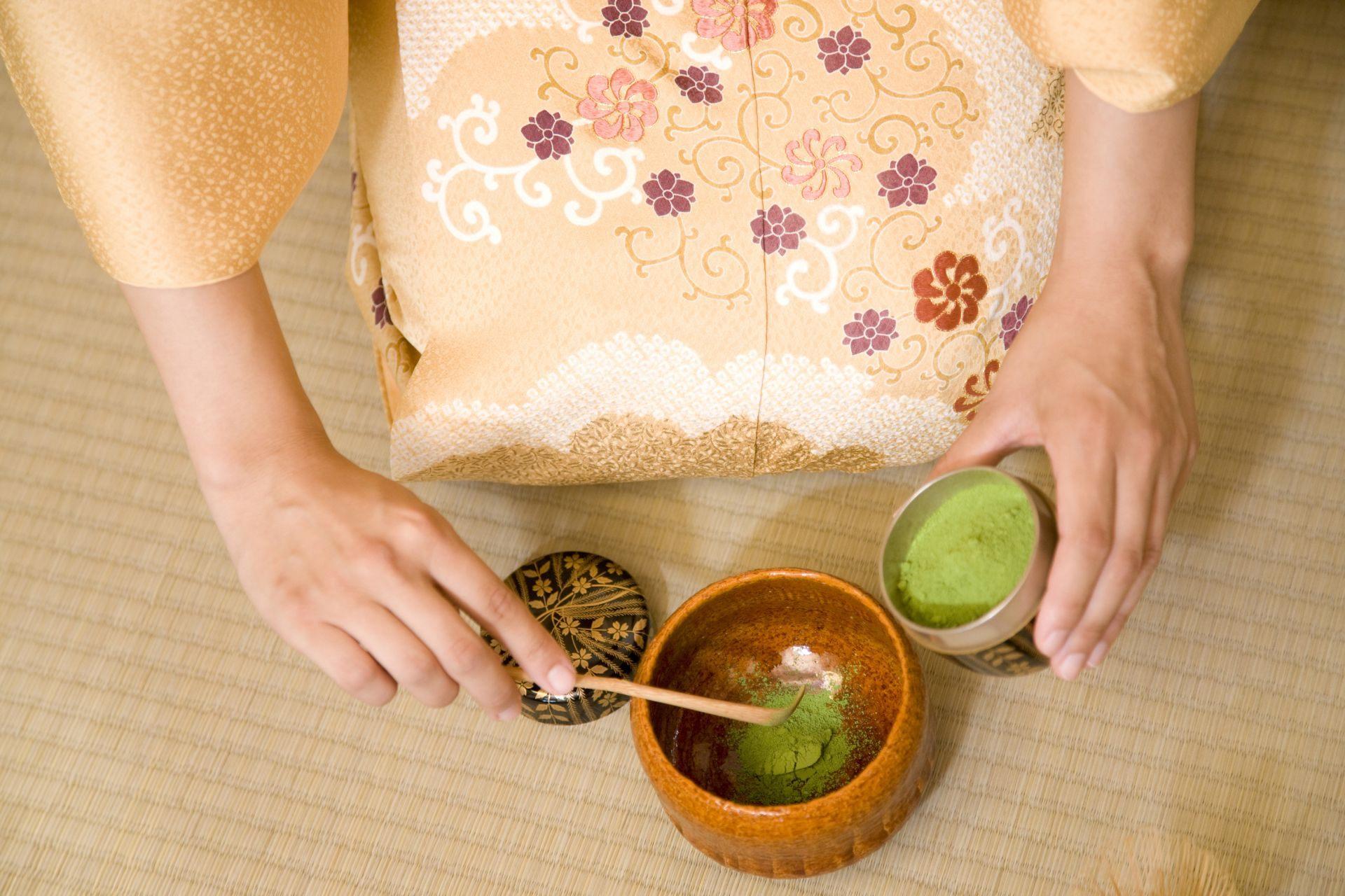 将磨好的抹茶从茶罐用茶杓缓缓放入茶碗