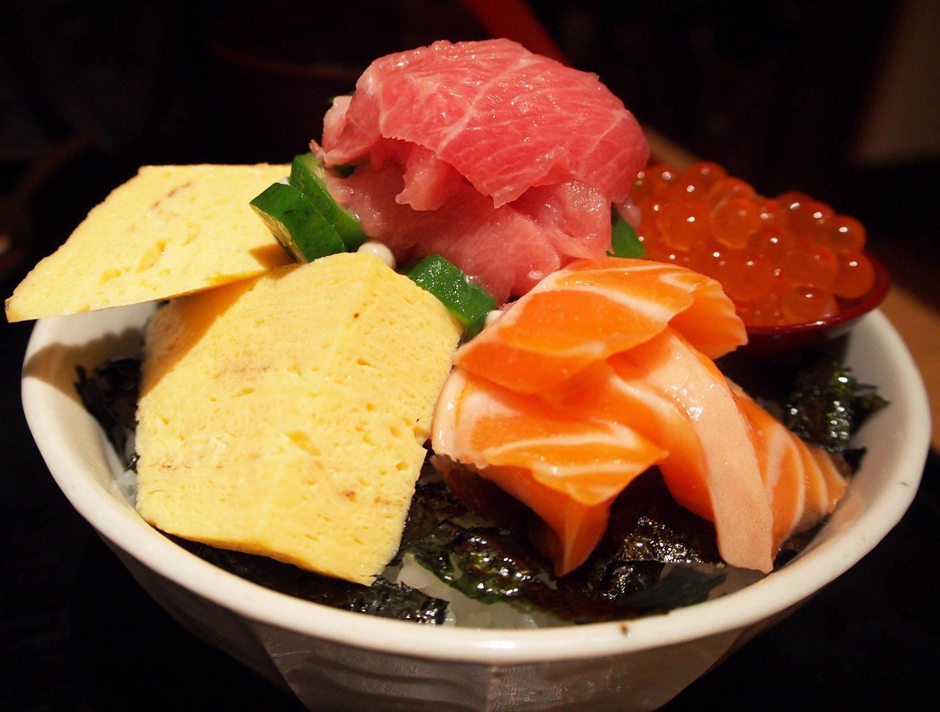 盖饭上堆着满满的鲑鱼、鲑鱼卵、真鲷、鲔鱼等高级海鲜食材