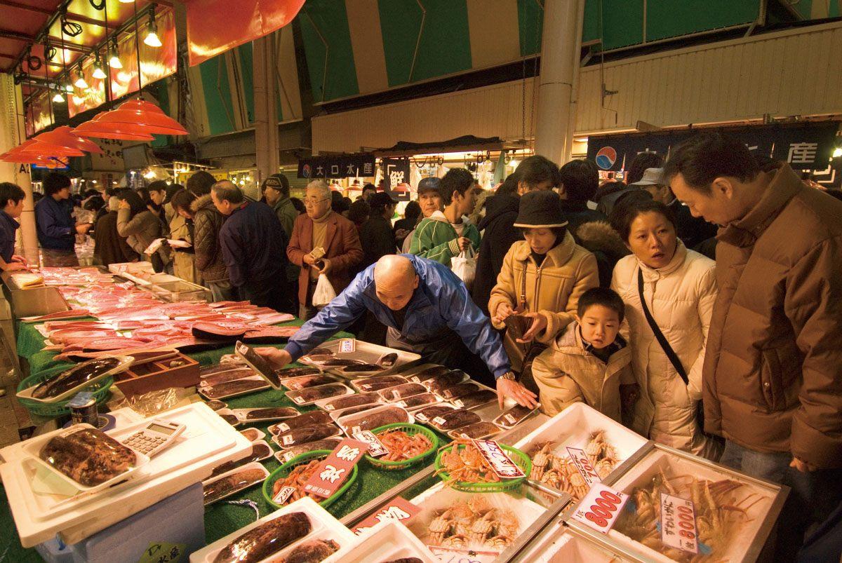 新鮮的魚肉與季節蔬菜在攤販上一列排開的近江町市場