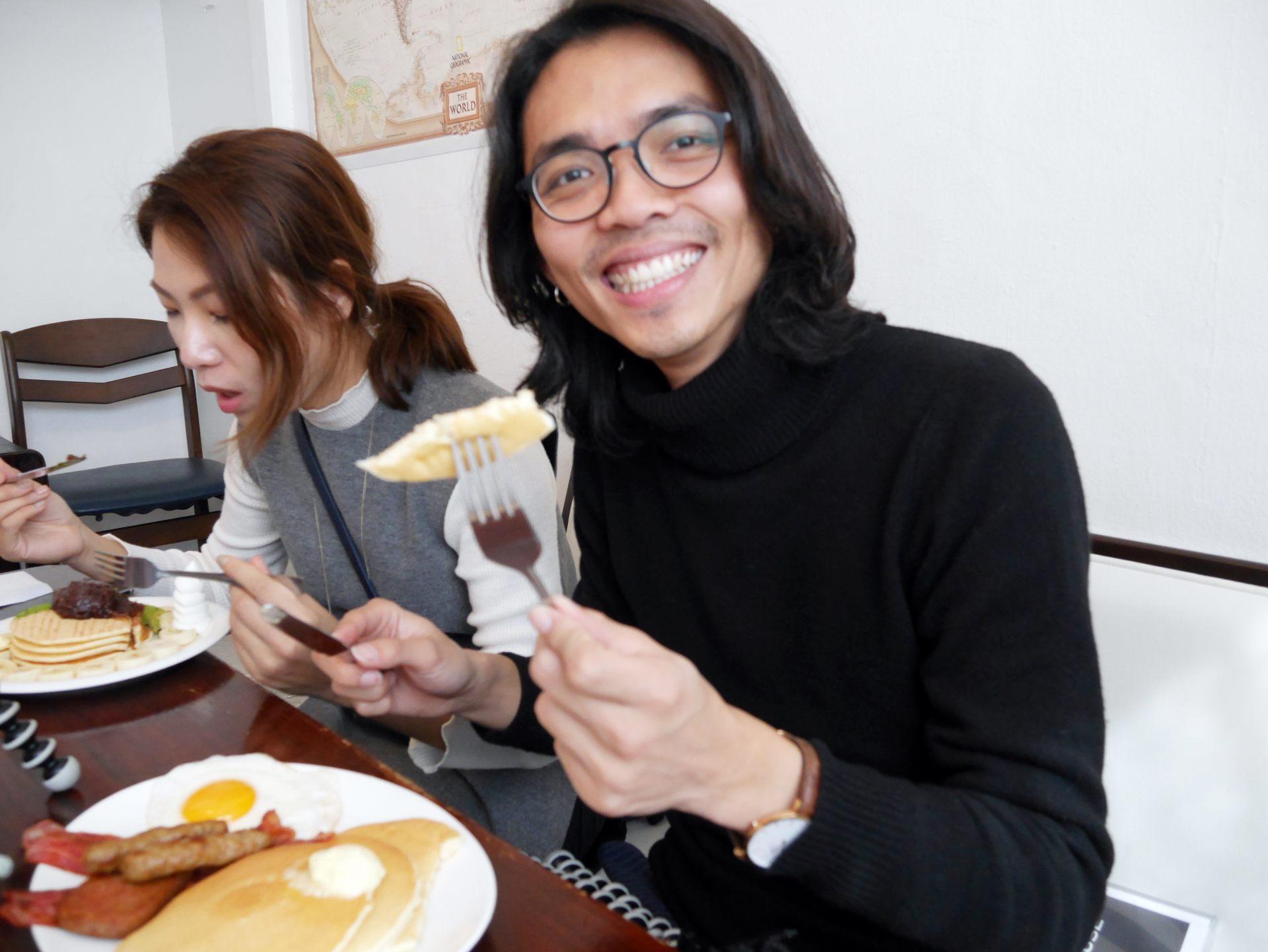 賴先生享用鬆餅的美味露出笑容