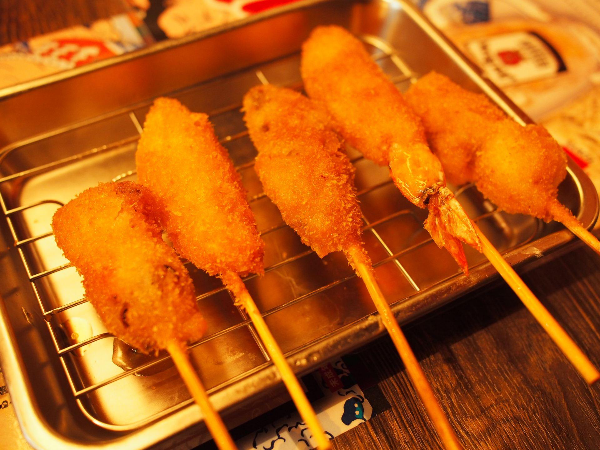 把肉和蔬菜等食材串在竹籤上,裹上麵衣後再用油炸的串炸豬排