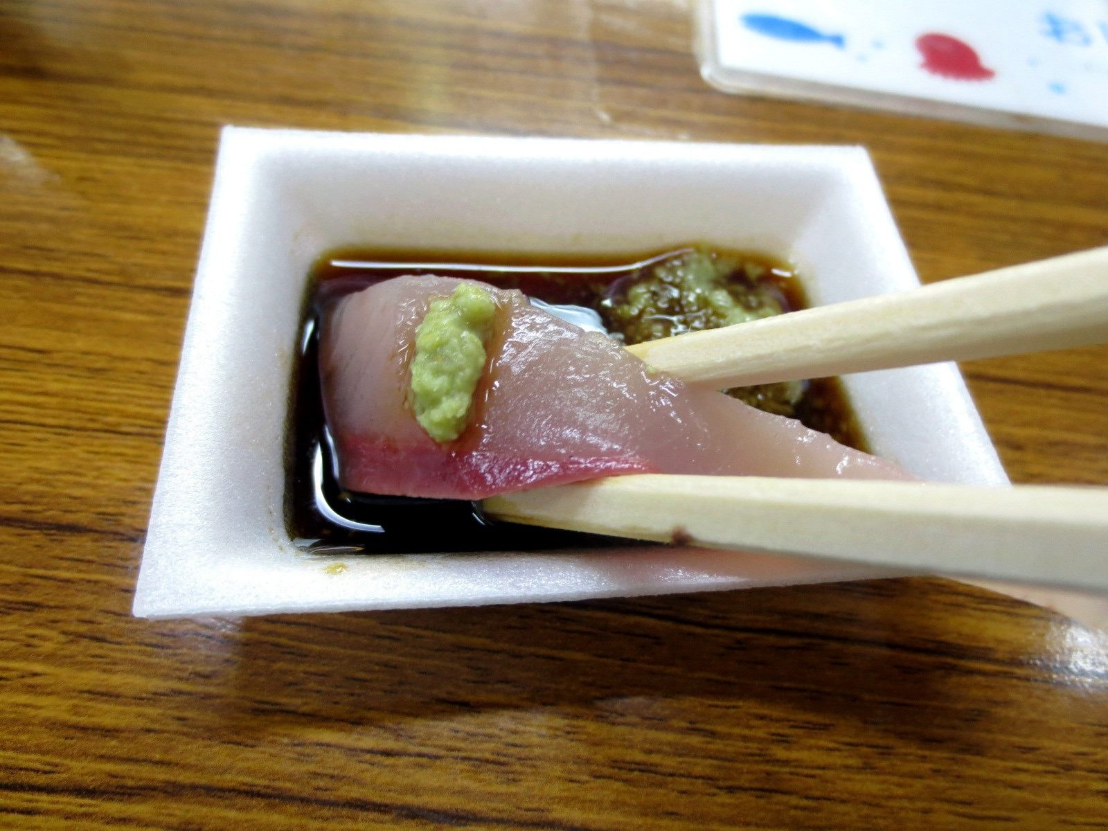 Eating it with wasabi and soy sauce