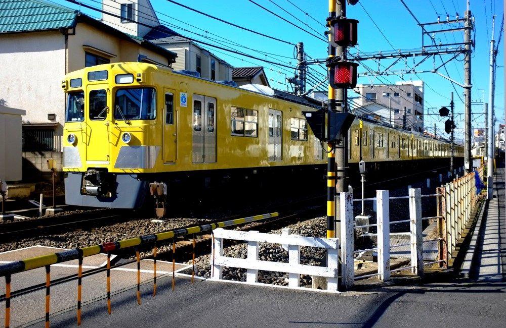 西武新宿線的黃色車廂在老街上悠閒行駛