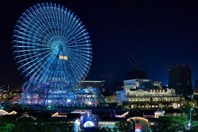 The Ferris wheel is lit up at night, making for a beautiful night view